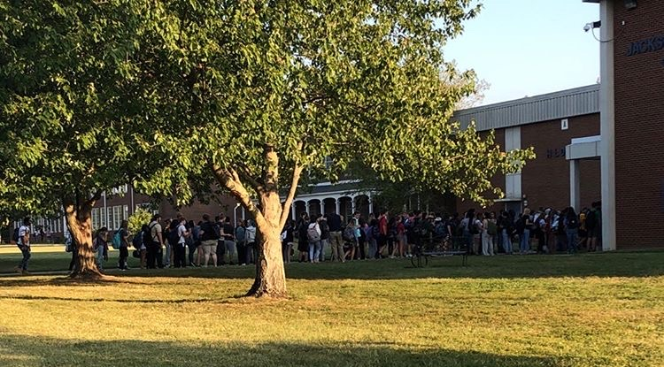 Students waiting in line  in front of the gym foyer.
