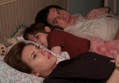 The broken family lays in a bed as they help their son fall asleep- showing that their son