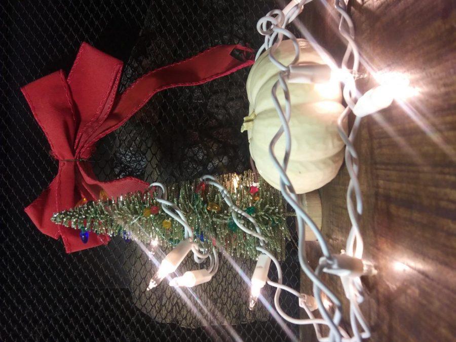Holiday lights wrapped around a pumpkin and a mini Christmas tree